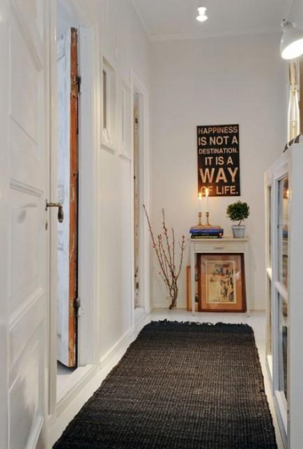 wąski przedpokój,biały przedpokój,korytarz,jak urzadzić wąski korytarz,biale ściany,skandynawski styl,nowoczesne mieszkanie,dekoracja holu,dekoracje do przedpokoju,typografie,czarny chodnik,dywan w przedpokoju,biała podłoga