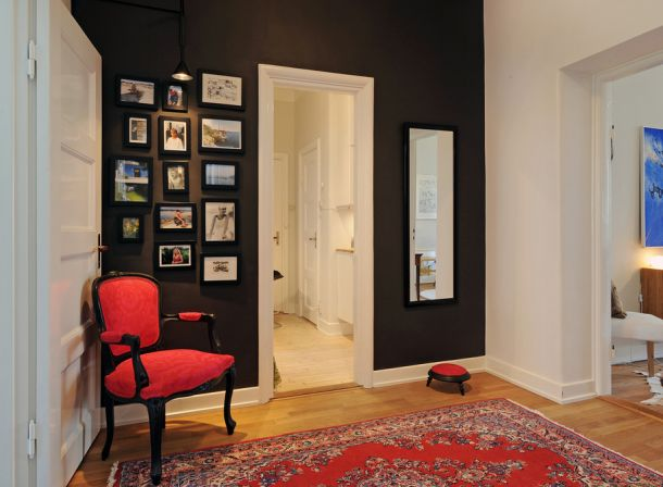 czarna ściana,czerwony dywan,ramki,galeria zdjęć w korytarzu,turecki dywan,wąski przedpokój,biały przedpokój,korytarz,jak urzadzić wąski korytarz,biale ściany,skandynawski styl,nowoczesne mieszkanie,dekoracja holu,dekoracje do przedpokoju,typografie,czarny chodnik,dywan w przedpokoju,biała podłoga