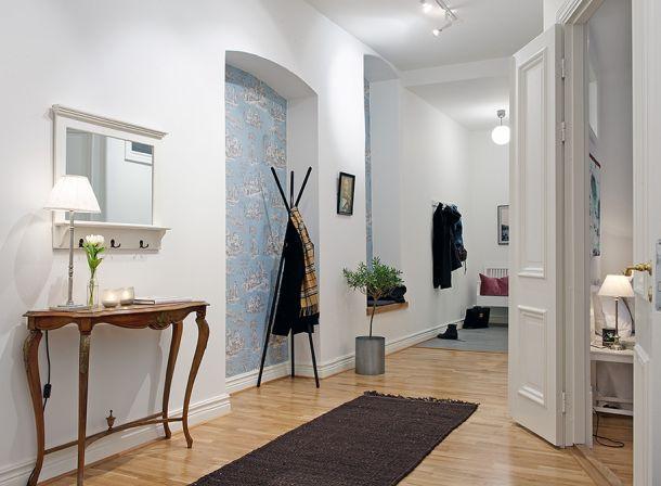 wzorzysta tapeta,wnęki w ścianach,stylowa konsolka,wieszak czarny nowoczesny,wąski przedpokój,biały przedpokój,korytarz,jak urzadzić wąski korytarz,biale ściany,skandynawski styl,nowoczesne mieszkanie,dekoracja holu,dekoracje do przedpokoju,typografie,czarny chodnik,dywan w przedpokoju,biała podłoga