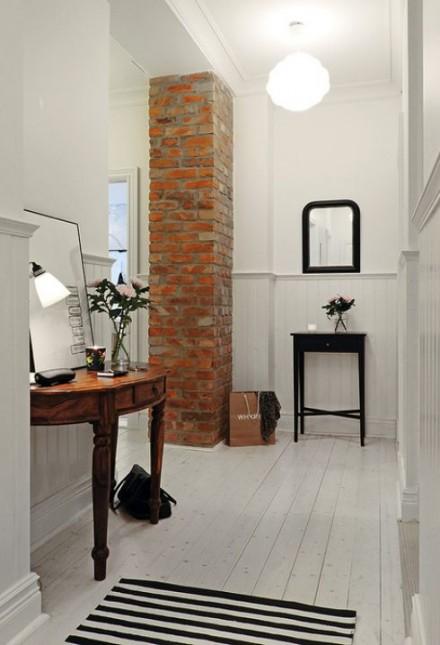 brazowa konsolka,półokragła konsolka,stylowa konsolka,czerwona cegła w korytarzu,czarny stolik,czarne lustra,czarnobiały chodnik,paski,pasiasty dywan,wąski przedpokój,biały przedpokój,korytarz,jak urzadzić wąski korytarz,biale ściany,skandynawski styl,nowoczesne mieszkanie,dekoracja holu,dekoracje do przedpokoju,typografie,czarny chodnik,dywan w przedpokoju,biała podłoga
