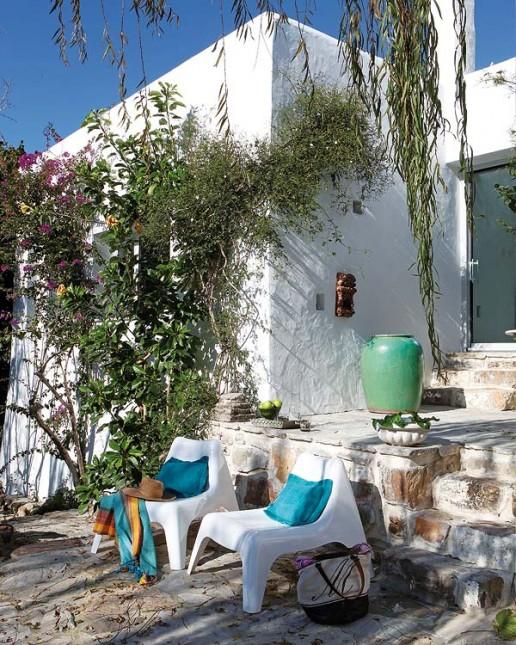 dom z kamienia,turkusowe wazony,turkusowe poduszki,białe,plastikowe fotele,turkusowo,pomarańczowy pled,śródziemnomorska aranżacja,kamienne dekoracje