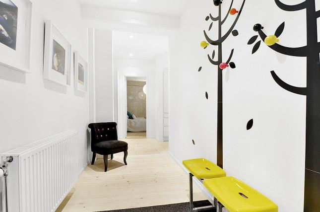 biały korytarz,skandynawski przedpokój,wejscie do mieszkania,żółte ławki,wieszak drzewka,oryginalny wieszak drzewka do holu,kolorowy wieszak,pomysł na wieszak do przedpokoju