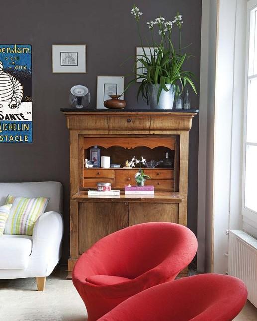 salon z grafitową, szarą ścianą ,czerwone fotele