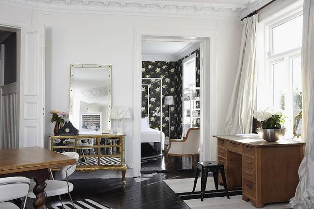 ekletyczne wnętrze,salon w mieszanym stylu,mix stylów w salonie,biało-brązowo-czarne mieszkanie,skandynawskie mieszkanie w mieszanym stylu,eklektyczna aranżacja,aranzacja skandynawskiego mieszkania,klasyczne meble,nowoczesne krzesła,czarno-białe dekoracje,czarna podłoga,dywan w pasy,skórzane krzesła,toczone nogi w stole,nowoczesne półki na książki,czarna tapeta w kwiaty