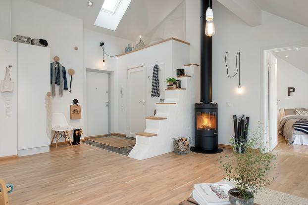 skandynawskie poddasze,aranzacja w stylu skandynawskim,loft po skandynawsku,piękny loft,jasna aranzacja mieszkania,białe wnętrza,skandynawski styl,miksowanie stylów,jak urządzić poddasze,jak łączyć style w mieszkaniu,ciekawe poddasza,ciekawe aranżacje wnętrz,dobre pomysly na urządzenie poddasza,otwarty salon na poddaszu,pokój z kominkiem,czarny kominek