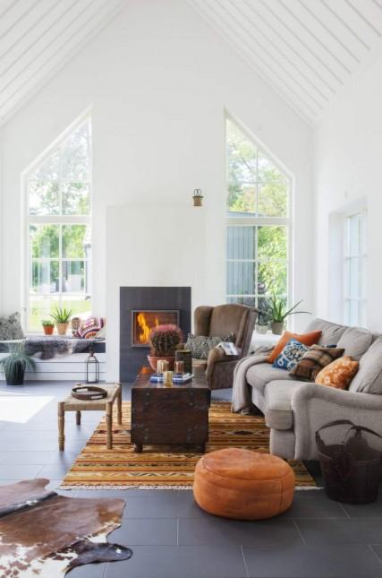 salon z kominkiem w eklektycznym stylu,aranzacja skandynawskiego domu w mieszanym stylu,skóra bydlęca,pomarańczowy dywan w etniczne wzory,pomarańczowy puf,drewniany kufer,skrzynia z okuciami,fotel brązowy,fotel uszak,szara sofa,