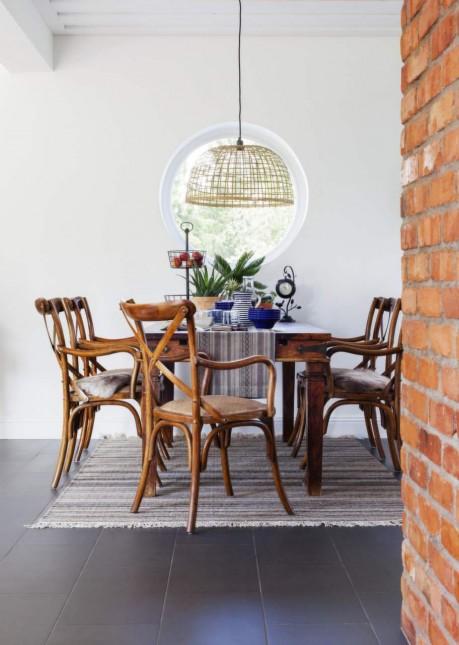 skandynawska jadalnia,ściana z czerwonej cegły,cegła na ścianie w jadalni,drewniany stylowy stó,krzesła z drewna gietego,skandynawskie krzesła z brązowego drewna,niebieska porcelana,biało-niebieska serweta na stole,ażurowa lampa wisząca,skandynawska lampa z rattanu,białe sciany,czarna podłoga w jadalni,skandynawski dziergany dywan,aranżacja w mieszanym stylu,rustykalny stól w jadalni