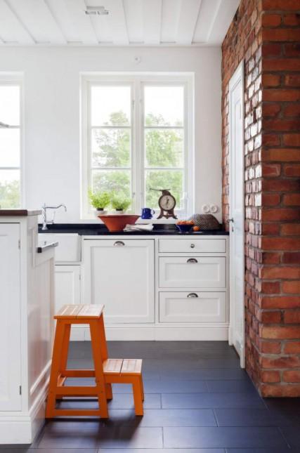 skandynawska kuchnia,biała kuchnia w stylu skandynawskim,ściana z czerwonej cegły,czarna podłoga,białe ściany,aranzacja białej kuchni,skandynawski styl we wnętrzach