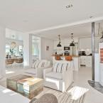 Przytulna aranżacja mieszkania w bieli z kominkiem i bielonymi cegłami