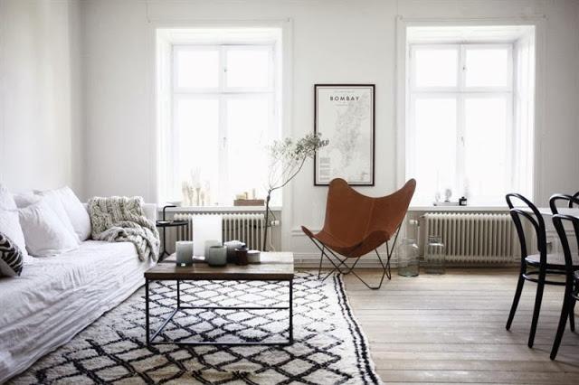 skandynawski salon,aranżacja skandynawskiego salonu,fotel butterfly,skórzany fotel w kształcie motyla,dizajnerski fotel ze skóry,ikony designu w salonie,biała sofa,tkany dywan,skandynawski dywan w marokańskim stylu,biało-czarny dywan z Maroka,industrialny stolik kawowy,meyalowy stolik z drewnianym blatem,salon z mieszanymi meblami,mix meblowy w salonie skandynawskim