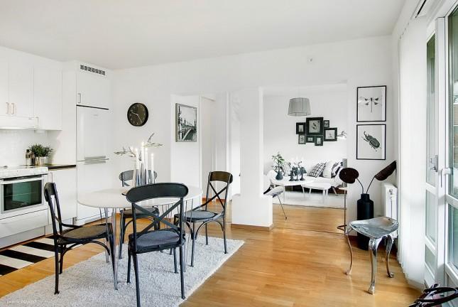 małe mieszkanie,otwarta zabudowa małego mieszkania,otwarta przestrzeń małego mieszkania,aranżacja otwartej przestrzeni w małym mieszkaniu,jak urzadzić małe mieszkanie w otwartej zabudowie,kuchnia z jadalnią i salonem razem w jednym pomieszczeniu,jak połączyć salon z kuchnią,otwarty salon z kuchnią i jadalnią,biało-czarne mieszkanie,aranżacja w biało-czarnych kolorach,biało-czarne wnętrza,wnętrza z czarnymi meblami i dekoracjami,biało-czarne dekoracje we wnętrzach,skandynawskie wnętrze,skandynawski styl,industrialne krzesła,nowoczesne meble w skandynawskich aranżacjach wnętrz,czarne krzesłą przy okrągłym białym stole,czarne rami vintage na białej ścianie,skandynawskie plakaty
