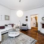 Białe skandynawskie mieszkanie o nieregularnym kształcie z cudowną podłogą z ciemnego drewna!