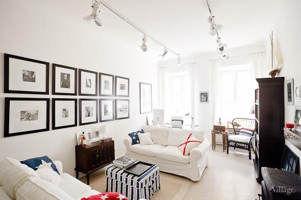 biały salon z galerią zdjęć w czarnych ramkach