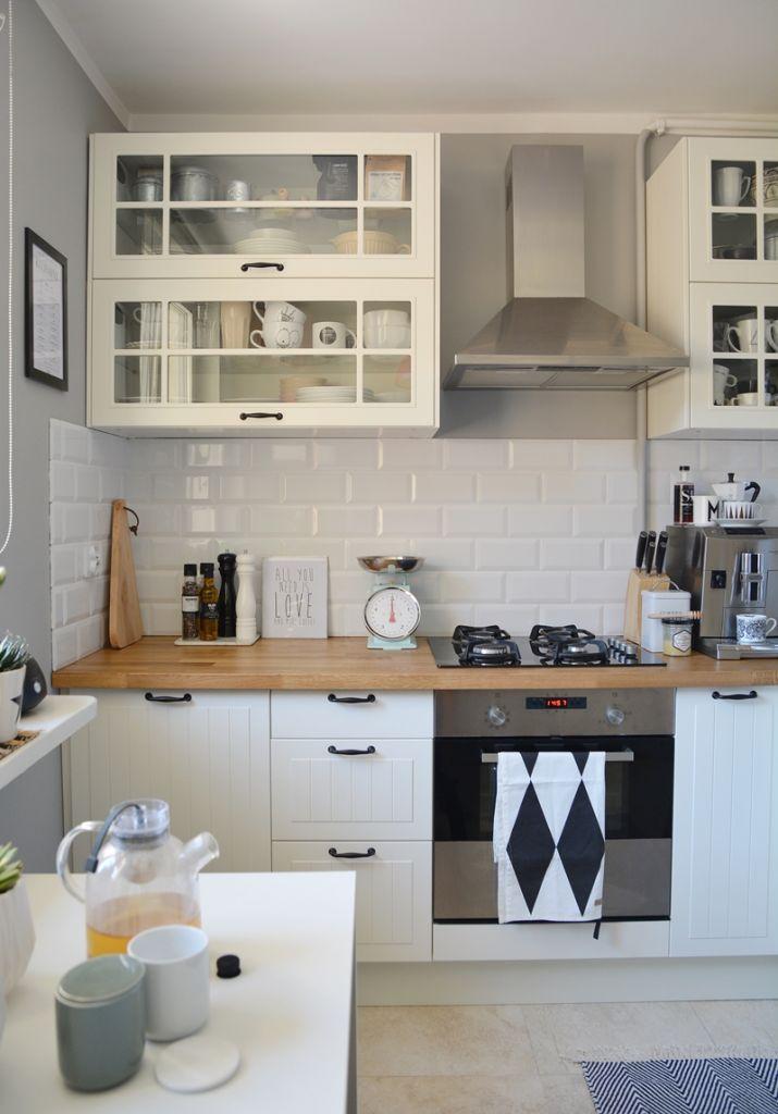 Białe szafki kuchenne z drewnianym blatem i płytkami ala